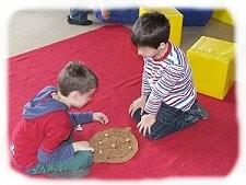 Kinder mit ihrem selbst gebastelten Kreismühlespiel